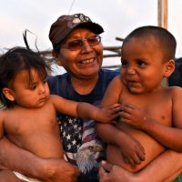 Beatrice Lookinghorse sits with two of her grandchildren on Cheyenne River reservation in South Dakota