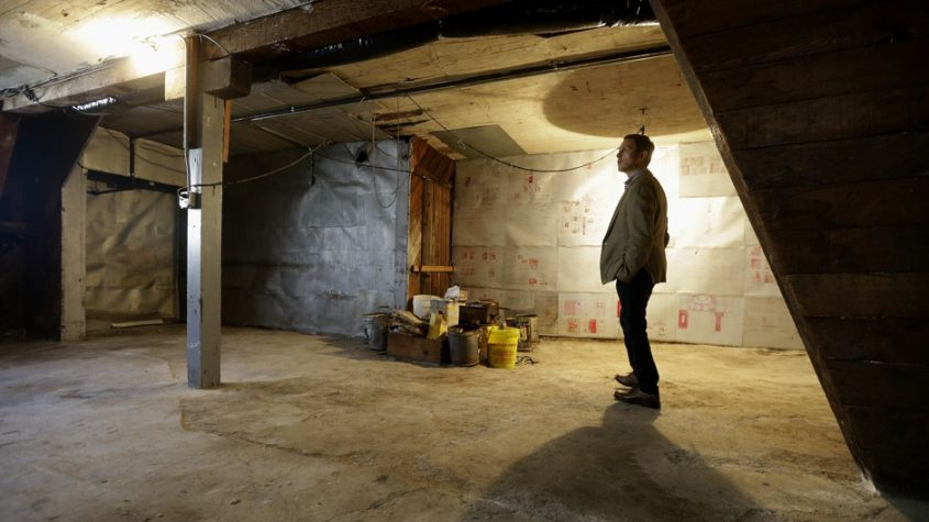 Man standing in unfinished garage