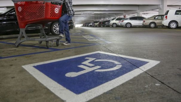 """Image of undercover police officer standing next to disabled parking spot to monitor for """"improper"""" use of disabled parking permits"""