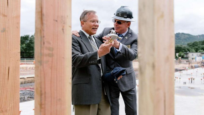 image of Mayor of Danville and handing the Town Manager a hammer at the ceremony of the construction site of new housing development