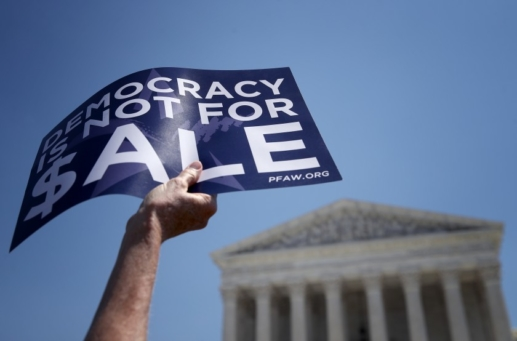 image of protestor holding sign that reads, Democracy is not for sale""