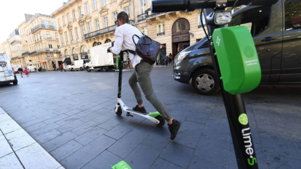 image of person riding a Lime scooter
