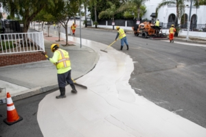 City workers apply a cooling paint on roads in Pacoima